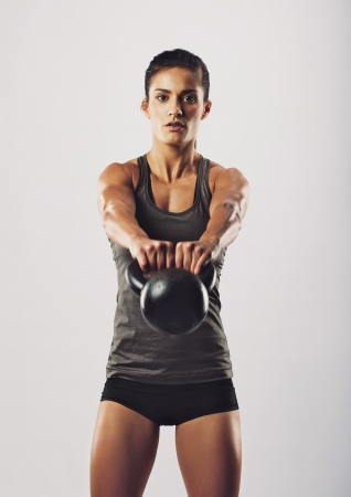 Young fit woman holding kettle bell exercising against grey background. Female fitness instructor looking at camera while exercising. photo
