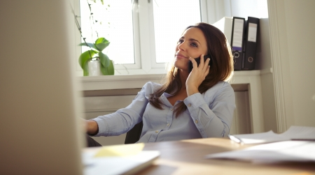 attractive female: Attractive young woman sitting at her desk talking on mobile phone. Pretty caucasian businesswoman working in home office. Stock Photo