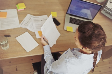 노트북을 책상에 앉아있는 동안 젊은 여자 검사 청구서의 상위 뷰입니다. 데스크에서 근무하는 백인 사업가.