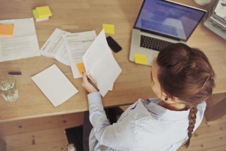 caucasico: Vista superior de una mujer joven, comprobaci�n de facturas mientras est� sentado en el escritorio con ordenador port�til. Empresaria cauc�sica de trabajo en el escritorio. Foto de archivo