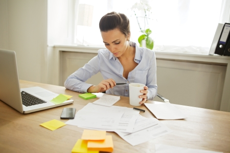 busy office: Attractive young woman working at the desk with sticky notes and laptop. Beautiful businesswoman reading notes while sitting in home office. Stock Photo