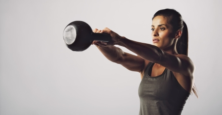 crossfit: Young fitness female exercise with kettle bell. Mixed race woman doing crossfit workout on grey background. Kettlebell swing. Stock Photo