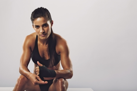 Woman boxer wearing black strap on wrist for boxing practice, Fitness female sitting getting ready for boxing practice. Beautiful young woman with muscular body preparing for workout. photo