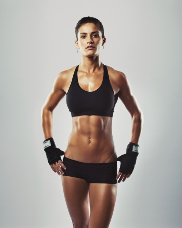 Portrait of sexy young woman with her hands on hips looking at camera. Fitness female with muscular body ready wearing hand gloves for workout on grey background