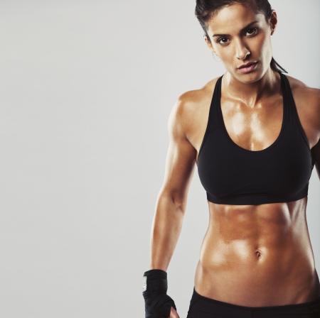 Foto van een fitness model op een grijze achtergrond. Jonge vrouw bodybuilder met gespierde lichaam op zoek naar camera met copyspace Stockfoto