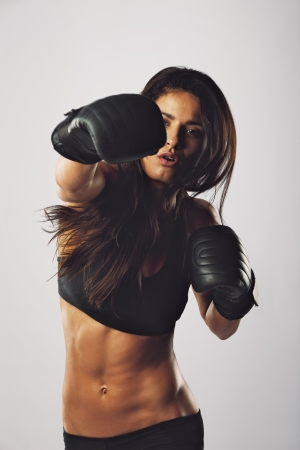 woman boxing gloves: Fit young woman wearing boxing gloves punching towards camera against grey background. Hispanic female boxer practicing boxing. Stock Photo