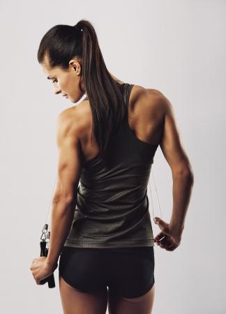 mujer deportista: Atleta femenina joven confidente con la cuerda de salto que presenta en fondo gris. Vista posterior de la mujer culturista espalda de pie sosteniendo la cuerda que salta. Foto de archivo