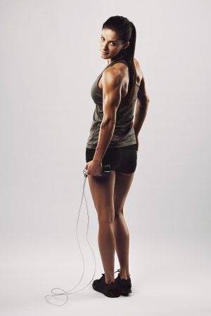 Vertical shot of young female exercises with a jump rope looking over shoulder at camera. Muscular woman exercising on grey background. Full body shot.