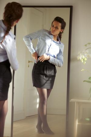 vistiendose: Empresaria joven hermosa que se fijan la falda delante del espejo. Modelo de mujer bastante cauc�sica vistiendo.