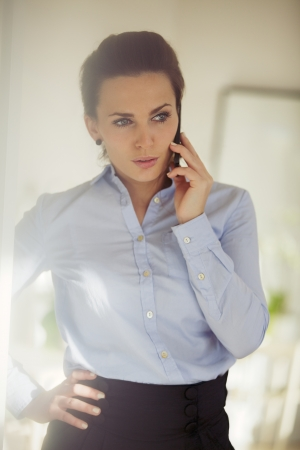 Confident young businesswoman talking business on the phone. Caucasian female using mobile phone looking away. photo