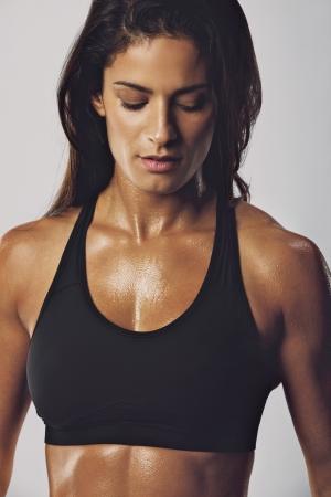 Portrait des mittleren Osten Frau in Sport-BH mit muskulösen Körper nach unten gegen grauen Hintergrund. Weibliche Bodybuilder-Modell.
