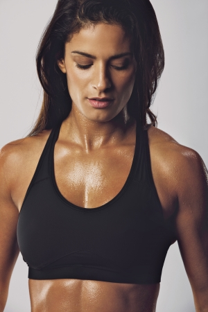 bra model: Portrait of middle eastern woman in sports bra with muscular body looking down against grey background. Female bodybuilder model.