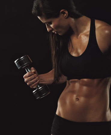 culturista: Modelo de fitness Mujer ejercicio con pesas. Culturista femenino joven que trabaja con pesas de mano en el fondo negro. Mujer con cuerpo musculoso.