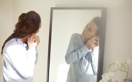 Beautiful female putting on her earring in front of mirror. Businesswoman getting dressed for work. Caucasian female model in blue shirt. photo