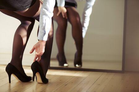 vistiendose: Primer plano de las piernas femeninas vistiendo zapatos de tacones altos. Mujer que ajusta los tacones altos frente al espejo.