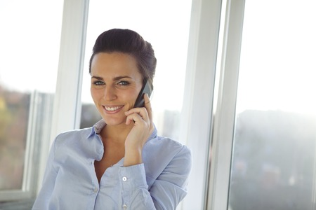 Cheerful young business woman standing in office talking on her mobile phone looking at camera. Beautiful caucasian female model using cell phone. photo