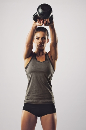 Young female doing swing exercise with a kettle bell. Fitness woman photo