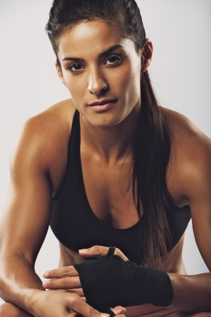 Confident young female boxer wearing strap on wrist. Boxing practice on grey background. Mixed race woman in sports clothing preparing for boxing fight or workout looking at camera.
