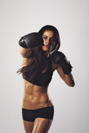 female boxing: Portrait of a young woman boxer throwing a punch at camera while practicing on grey background. Mixed race female athlete wearing boxing gloves exercising boxing.