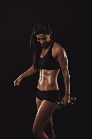 Female fitness model exercising with dumbbell. Happy young woman lifting weights for body building training over black background. Sexy muscular weightlifting woman.