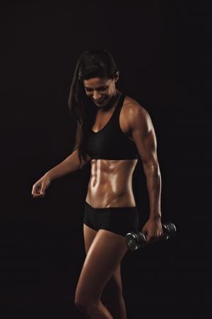 pesas: Modelo de fitness Mujer ejercicio con pesas. Mujer joven feliz levantando pesas para el entrenamiento del edificio del cuerpo sobre el fondo negro. Sexy mujer de levantamiento de pesas muscular.