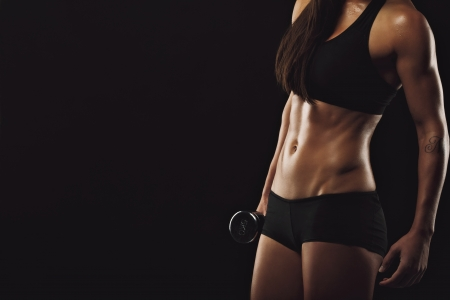 Cropped image of young female bodybuilder holding dumbbell against black background with copyspace. Fitness woman exercises with weights. Muscular body with perfect abs.