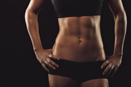 Close up of fit womans torso with her hands on hips. Female with perfect abdomen muscles on black background Stock Photo