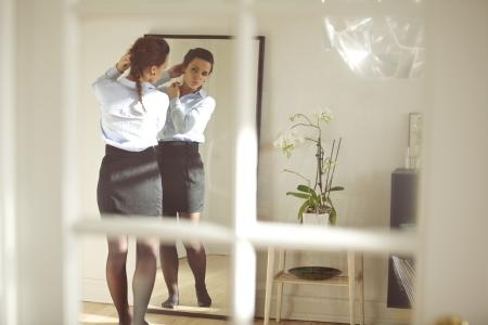 vistiendose: Hermosa mujer de negocios que consigue vestido para el trabajo frente al espejo en su casa. Modelo de mujer de raza cauc�sica en traje de negocios. Tiro sincero. Foto de archivo