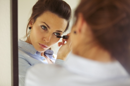 Pretty female looking in mirror and putting on mascara, Businesswoman applying makeup. Caucasian female model getting ready. photo