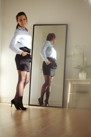 full length mirror: Confident young businesswoman standing in front of mirror looking at camera posing. Beautiful young caucasian female model posing.