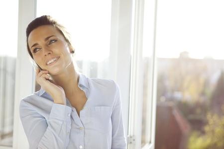 zelle: Junge Unternehmerin auf Handy, während stehend von Fenster im Amt. Schöne junge weibliche Modell in hellen Büro. Lizenzfreie Bilder