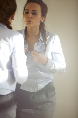 Pretty young business woman buttoning up her shirt in front of mirror. Caucasian female model getting dressed for office at home. Stock Photo