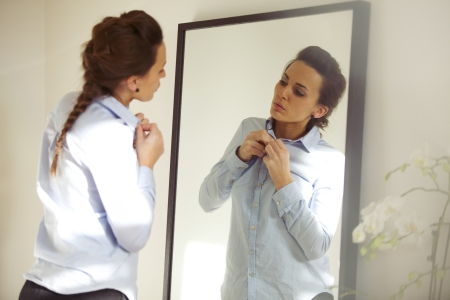Attractive young woman in front of mirror buttoning up her shirt. Beautiful caucasian female getting dressed for office. photo