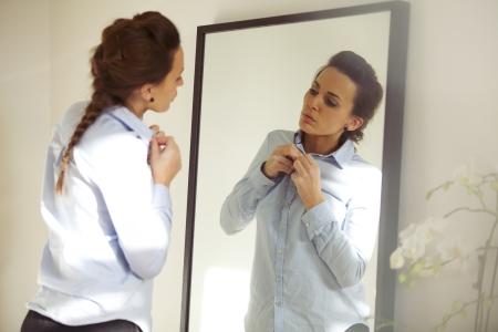 Attraente giovane donna di fronte a specchio abbottonarsi la camicia. Bella caucasica donna vestirsi per ufficio.