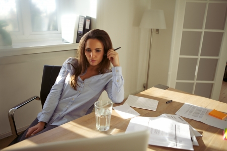 Young businesswoman thinking about the new business plan. Beautiful young woman sitting at her desk with laptop working from home. photo