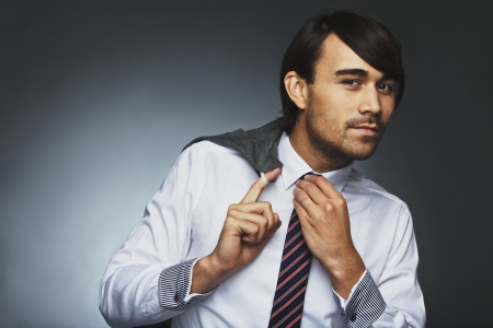 Asian businessman posing against grey background. Young male model holding his jacket and adjusting his necktie. photo