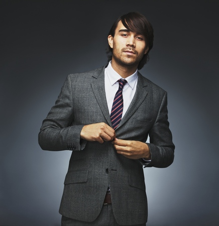 Portrait of handsome young male model buttoning coat. Attractive businessman getting dressed. Mixed race male model on black background. photo