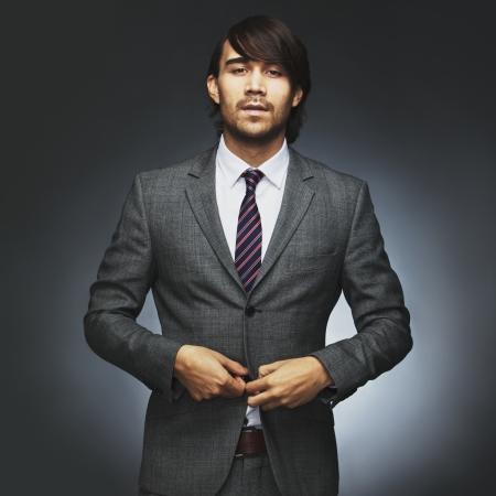 세련된 양복을 입고 매력적인 젊은 남성 모델의 초상화입니다. 사업가 작품에 대한 읽기지고. 검은 배경에 코트를 단추를 끼우는 아시아 사업가. 스톡 콘텐츠 - 25195522