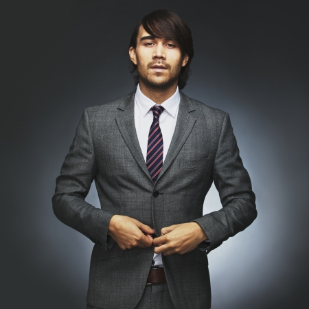 Portrait of attractive young male model wearing stylish suit. Businessman getting read for work. Asian businessman buttoning coat on black background.