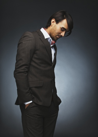 Attractive young man in stylish suit standing on black background. Male fashion model with hands in pocket looking down in thinking. photo