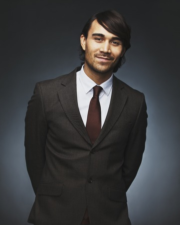 Portrait of charming young businessman looking at camera smiling. Well dressed asian male model posing against black background photo
