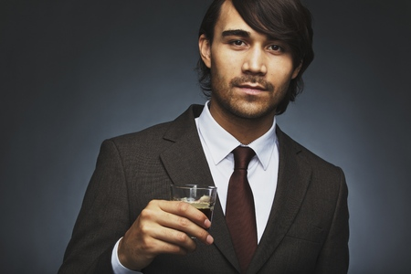 Closeup portrait of attractive young man in business suit holding a cup of coffee in hand. Asian male business executive having coffee. Young male fashion model on black background with coffee. photo