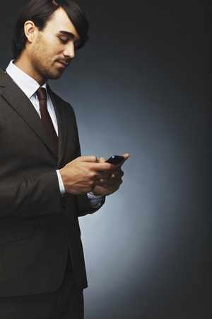 Portrait of young businessman text messaging using mobile phone on black background. Asian male model using cell phone. photo