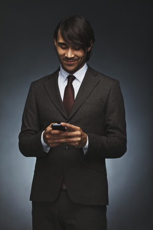 Happy young executive texting on his smart phone. Handsome male associate reading test message on his cell phone. Male model in business suit holding mobile phone on black background. photo