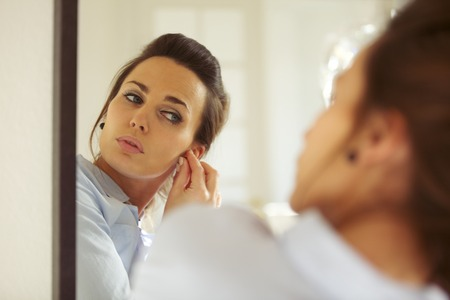 putting on: Attractive young woman putting on her earrings while looking at the mirror. Caucasian businesswoman getting dressed. Female model Stock Photo