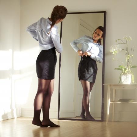 pansement: Jolie jeune femme d'affaires, fixant sa jupe devant le miroir. Beau mod�le caucasien femelle pr�t pour le travail. Banque d'images