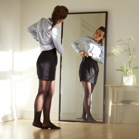 Pretty young businesswoman fixing her skirt in front of mirror. Beautiful caucasian female model getting ready for work.