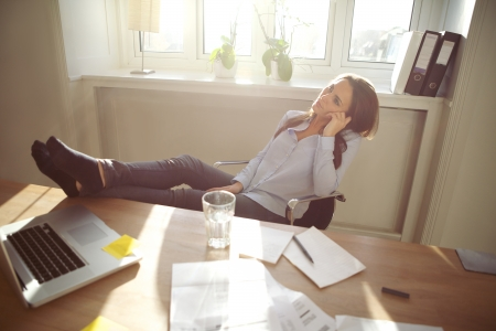 Young business woman sitting at her desk in office with her legs on the desk. Caucasian female relaxing and looking up in home office. photo