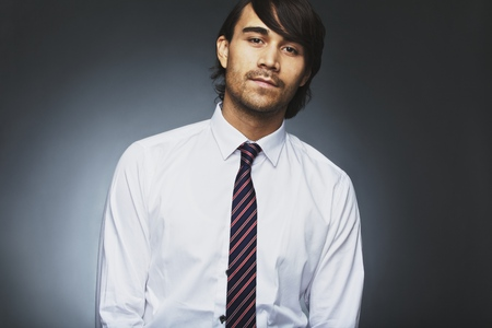Portrait of handsome young male business executive staring at camera against grey background. Asian young business. Male model wearing shirt and necktie. photo