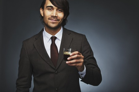 Portrait of happy young business man offering you a cup of coffee against black background. Mixed race male model holding black coffee. photo